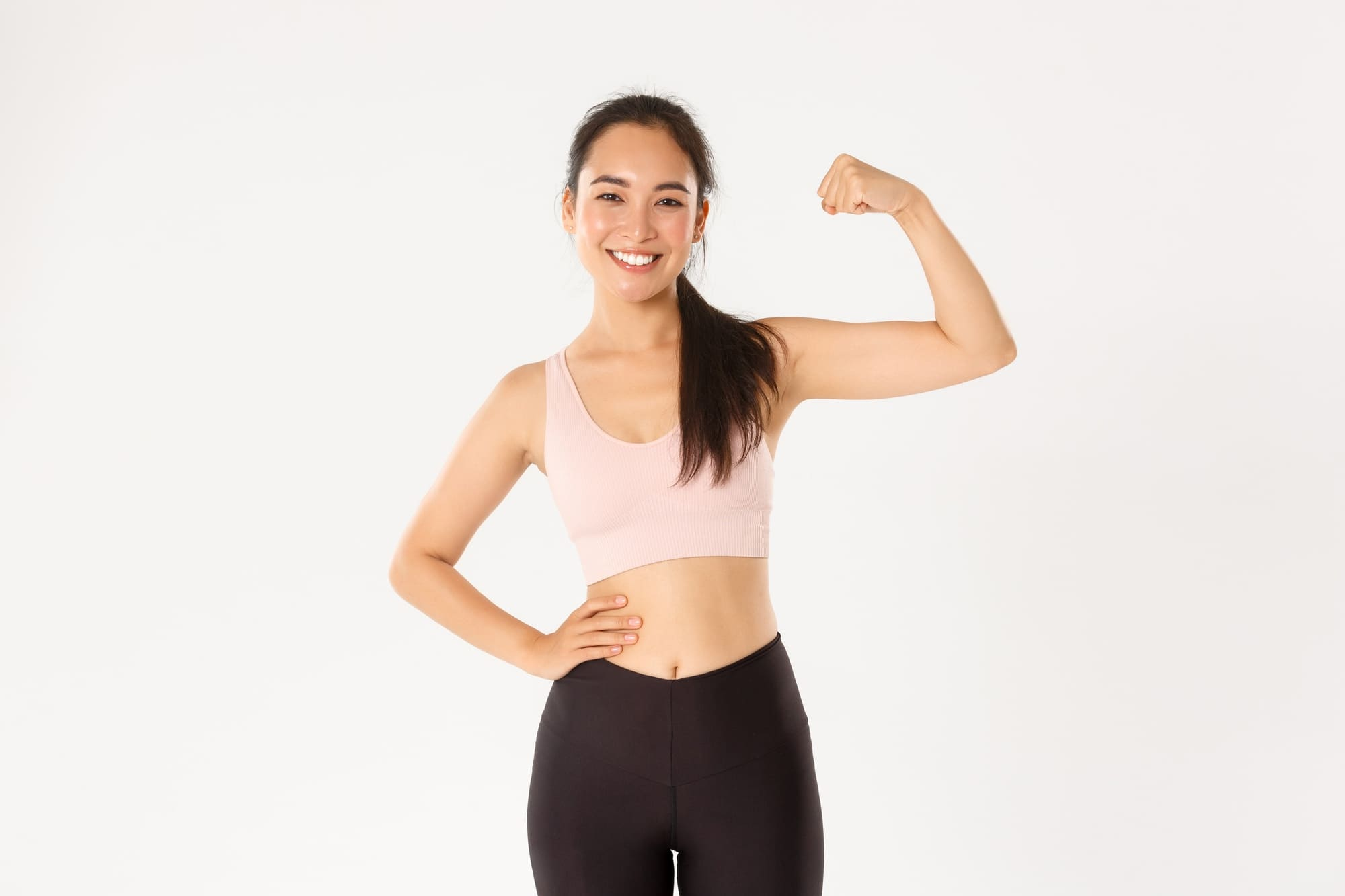 sport-wellbeing-and-active-lifestyle-concept-portrait-of-smiling-slim-and-strong-asian-fitness-girl-personal-workout-trainer-showing-muscles-flexing-biceps-and-look-proud-white-background (1)